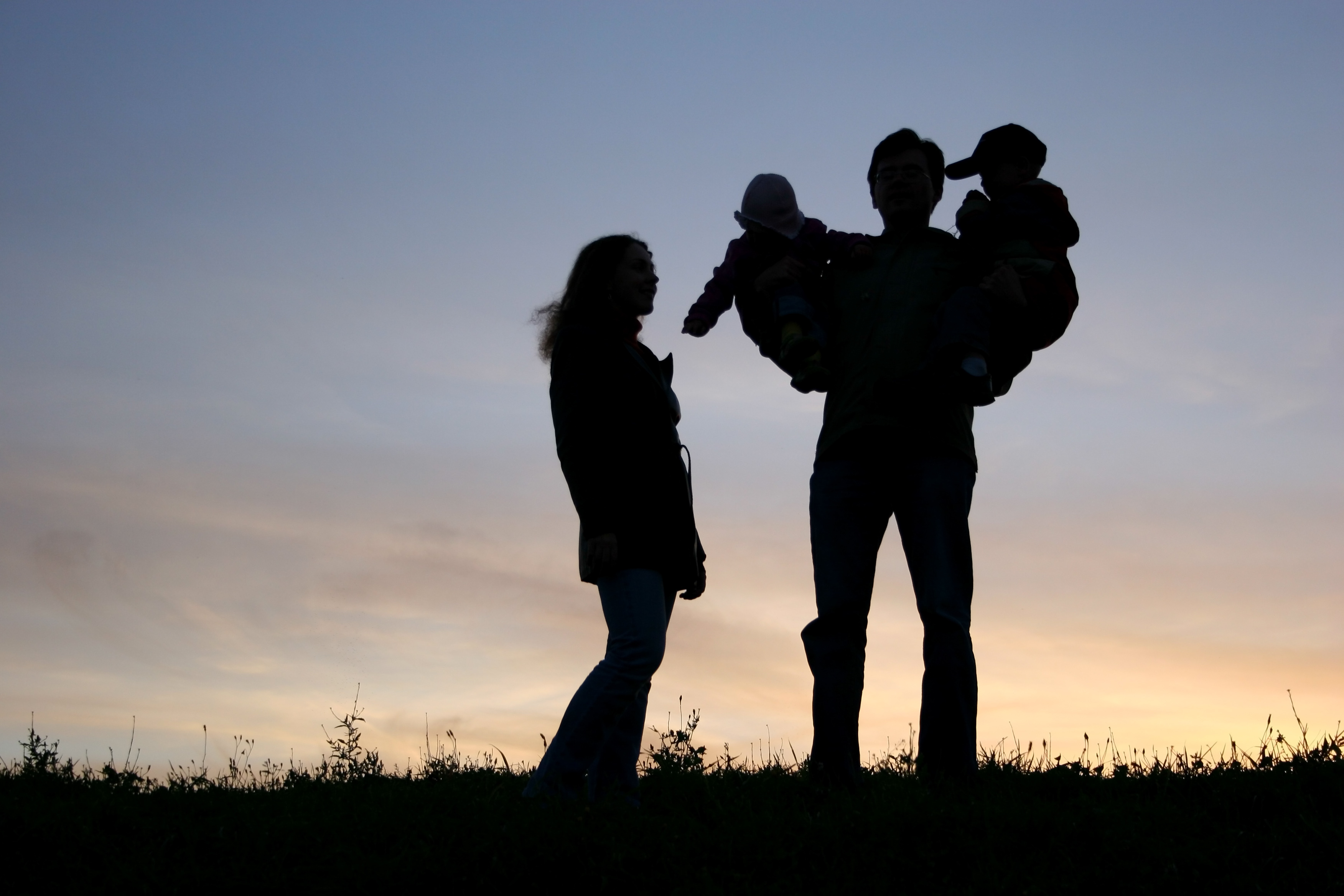 family with children on hands, sunset sky